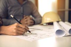 Zwei Technikmann oder Mitarbeiter, die an einem Projekt arbeiten und zusammen mit dem Betrachten von Planschreibarbeit sich bespr stockfotografie