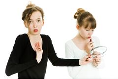 Zwei teenaged Mädchen feilschen, um einen Spiegel zu erhalten, um zu machen, - Schwesterrivalität zu bilden lizenzfreie stockfotos