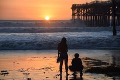 Zwei Teenager passt den Sonnenuntergang durch den Pier auf lizenzfreies stockfoto