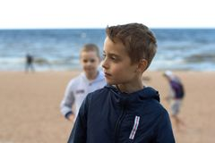 Zwei Teenager stehen auf dem Strand durch das Meer Bruderwegal Lizenzfreie Stockfotografie