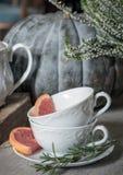 Zwei Teeschalen mit Rosmarin und Pampelmuse auf dem Hintergrund eines großen Kürbises und der Heide stockfoto