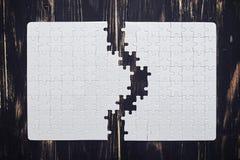 Zwei Teile eines Puzzlespiels auf dunklem hölzernem Schreibtisch Lizenzfreie Stockbilder