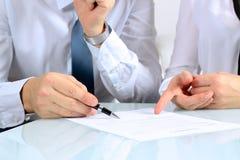 Zwei Teilhaber, die ein Dokument unterzeichnen Stockbild