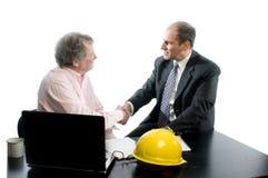 Zwei Teilhaber am Schreibtisch, der Hände rüttelt Stockbild
