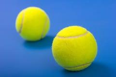 Zwei Tenniskugeln auf einem blauen Hintergrund Stockfotos