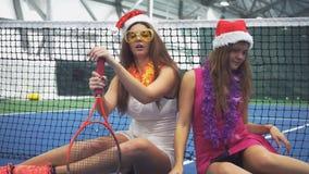 Zwei Tennisspieler in den Zusätzen des neuen Jahres sitzen auf dem Tennisplatz stock video footage