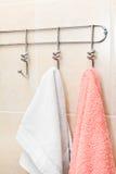 Zwei Terry-Tücher, die an Haken hängen Stockbilder