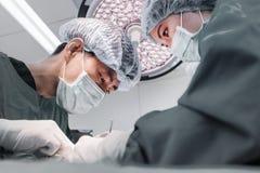 Zwei tierärztliche Chirurgen im Operationsraum Stockbilder