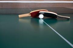 Zwei Tischtennisschl?ger und ein Ball auf einer gr?nen Tabelle Tischtennisnetz lizenzfreie stockfotos
