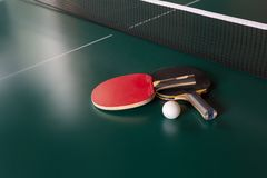 Zwei Tischtennisschl?ger und ein Ball auf einer gr?nen Tabelle Tischtennisnetz stockfotografie