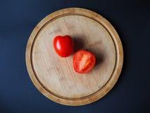 Zwei Tomaten auf der Draufsicht des runden hölzernen Schneidebretts stockbild
