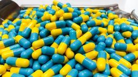 Zwei Ton Medizin-Kapseln auf Edelstahl mischen den Behälter Drogen bei, gelb Lizenzfreie Stockbilder