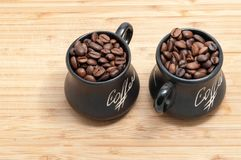 Zwei tonten Schalen mit Kaffeebohnen auf hölzerner Planke stockfoto