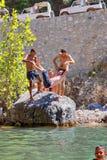 Zwei Touristen, die seinem Begleiter in einem Berg geworfen werden, strömen lizenzfreie stockfotografie