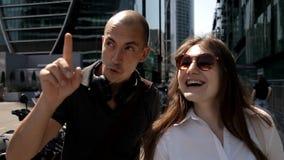 Zwei Touristen gehen um die Großstadt auf der Straße mit Wolkenkratzern und mit vielen Parkmotorrädern und genießen stock video