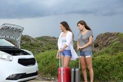 Zwei Touristen mit einem Zusammenbruchauto lizenzfreies stockbild