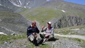 Zwei Touristen speisen in den Bergen mit Alkohol stock video