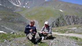 Zwei Touristen speisen in den Bergen mit Alkohol stock footage