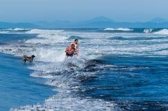 Zwei Touristen und ein Hund werden in den Wellen der Brandung schwimmen Lizenzfreie Stockfotos