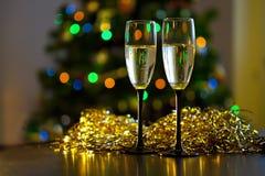 Zwei transparente Gläser Champagner mit Blasen im Hintergrund des Lamettas oder des sequinswo Stockfotos