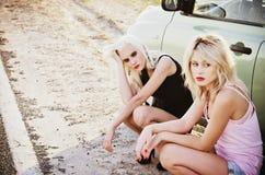 Zwei traurige schöne blonde Mädchen, die nahe defektem Auto und Wartehilfe sitzen Stockbilder