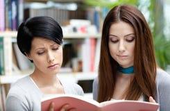 Zwei traurige Studenten gelesen an der Bibliothek Stockbilder
