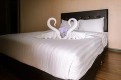 zwei Tuchschwäne geformt auf das Bett Stockbild