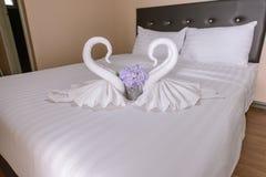 zwei Tuchschwäne geformt auf das Bett Lizenzfreies Stockbild