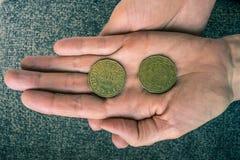 Zwei tunesische Münzen auf dem woman& x27; s-Palme Stockbilder