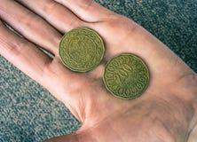 Zwei tunesische Münzen auf dem woman& x27; s-Palme Lizenzfreie Stockfotos