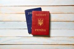 Zwei ukrainische Pässe, die auf einem Holztisch liegen Stockbild