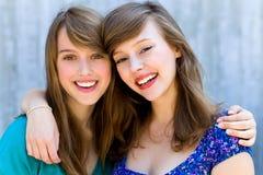 Zwei umarmende und lächelnde Frauen Stockfotografie