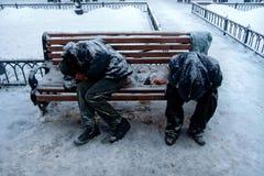 Zwei unerkennbare schmutzige obdachlose Männer oder Alkoholiker oder Drogenabhängigen schlafen auf Bank im kalten Winter lizenzfreies stockbild