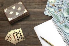 Zwei ungeöffnete Spielkarte-Plattform, Geld und Notizblock auf Tabelle stockbilder