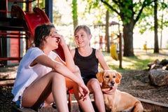 Zwei Unterhaltungsmädchen und Hund auf einem Spielplatz im Sommer Lizenzfreies Stockfoto