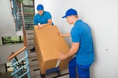 Zwei Urheber mit Kasten auf Treppenhaus stockfoto