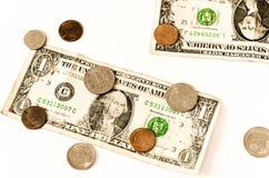 Zwei USA-Dollar und -münzen gelegt über Weiß Lizenzfreie Stockfotos