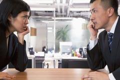 Zwei verärgerte Geschäftsleute, die entlang einander über einer Tabelle anstarren Stockbild