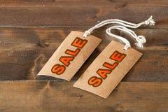 Zwei Verkaufsaufkleber auf einem Holztisch Lizenzfreies Stockfoto