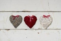 Zwei verklemmte Innere Abbildung der roten Lilie Drei Herzen auf altem weißem hölzernem Lizenzfreie Stockbilder