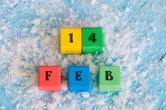 Zwei verklemmte Innere Kalendertag an den Farbhölzernen Würfeln mit markiertem Datum von 14 von Februar Stockfotos