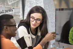 Zwei verschiedene Arbeitskollegen, die Anmerkungen beim zusammen sitzen an einem Tisch in einem modernen Büro lächeln und notiere Stockfotos