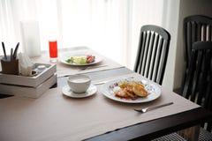 Zwei verschiedene Frühstücke werden in den restornae gedient Käsekuchen und Eier mit Würsten Stockbilder