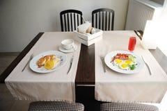 Zwei verschiedene Frühstücke werden in den restornae gedient Käsekuchen und Eier mit Würsten Lizenzfreies Stockfoto