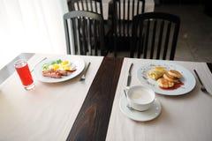 Zwei verschiedene Frühstücke werden in den restornae gedient Käsekuchen und Eier mit Würsten Lizenzfreie Stockfotografie