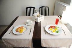 Zwei verschiedene Frühstücke werden in den restornae gedient Käsekuchen und Eier mit Würsten Lizenzfreie Stockbilder