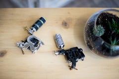 Zwei verschiedene kundenspezifische Berufstätowierungsgewehre vereinbarten auf einer Draufsicht des Holztischs Stockfotos