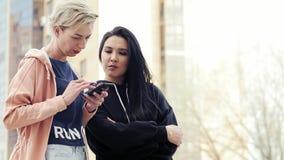 Zwei verschiedene Nationalitäten der jungen Frauen, multiethnische Freunde, die einen Smartphone verwenden stock video footage