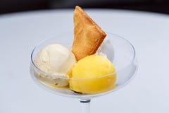 Zwei verschiedene Schaufeln Eiscreme mit Kuchen und Maracuja in einem Glas Stockbild