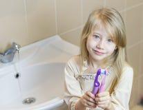 Zwei verschiedene Zahnbürsten küssen das Mädchen in seinen Händen Lizenzfreies Stockbild